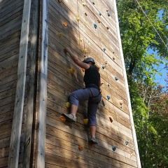 Climbing up a wall with harness and helmet on