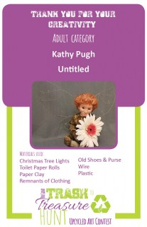 Trash to Treasure submission of a red-haired fairy man with wire wings holding a flower made of Christmas tree lights, toilet paper rolls, paper clay, remnants of clothing, old shoes & purse, wire, and plastic